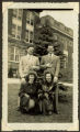 Two women and two men posed outside Old Main