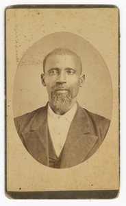 Photograph of a man with a beard wearing a dark colored suit and vest
