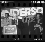 John B. Anderson at podium with Paul Winfield and Cecil Williams during presidential campaign in San Francisco, Calif., 1980