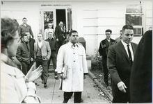 Hamilton Holmes, one of the first two African-American students to integrate the University of Georgia, leaving a campus building in Athens, Georgia, January 1961. White male students are shown in the background