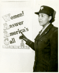 """African American Charity Adams, First Officer in the Women's Army Auxiliary Corps, standing in uniform and pointing to a poster that reads, """"Women! Answer America's Call, Serve in the W.A.A.C."""""""