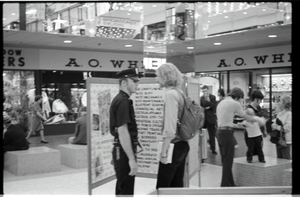Free Spirit Press crew member talking with police office in an indoor mall