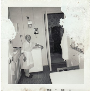 Elderly housekeeper poses in the kitchen
