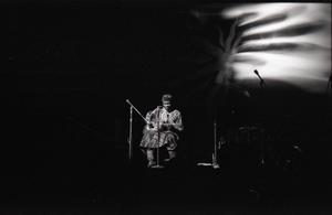 Taj Mahal in concert at Northfield, Mass.: Taj Mahal seated, playing guitar