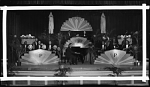 """[Group of musicians with instruments on stage with sign, """"Pals of Pleasure"""" : cellulose acetate photonegative, banquet camera format]"""