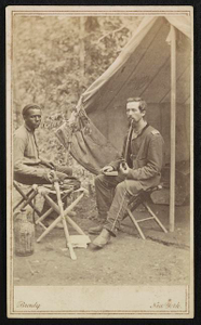 [Unidentified soldier of 23rd New York Infantry Regiment smoking a pipe and unidentified African American man, probably a servant, with sword, sitting in front of tent]