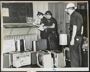 Police at Gates Ave. station in Brooklyn check loot, including several portable television sets, that had been confiscated from rioters