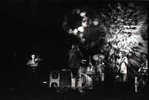 Hot Tuna concert: Band in performance on stage: Papa John Creach (violin), Will Scarlett (harmonica), Jorma Kaukonen (guitar), Jack Casady (bass) playing in front of light show