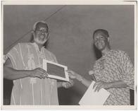 Jitu Weusi receiving a certificate from Mensah Wali