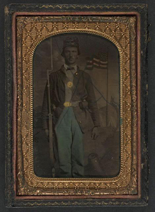 [Unidentified soldier in Union uniform and forage cap with bayoneted musket in front of painted backdrop showing military camp]