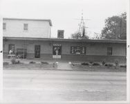Mississippi State Sovereignty Commission photograph taken from across the street of the front entrance to Stanley's Cafe and Trailways bus depot with two men standing outside, Winona, Mississippi, 1961 November 1