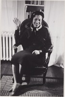 Photograph of Zora Neale Hurston seated and waving her hand