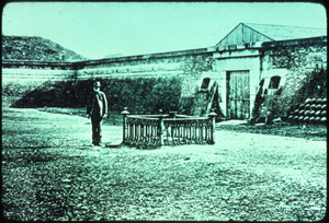 A very old picture of a man standing beside Osceola Cemetery at the entrance of Fort, Fort Moultrie, South Carolina