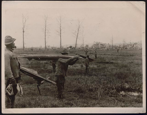 """The """"skirmish line"""" searching for the lost graves ... Company A, 321st Labor Battalion, spread out in """"skirmish line"""" formation by twos, searching for dead along the south bank of the Vesle in the Chateau-Thierry section. The stretchers are used to transport the bodies to the cemeteries /"""