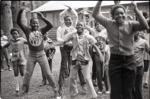 Inner City Round Table of Youth campers: group of African American children at summer camp, posed by camp building, raising hands and jumping