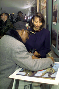 """A former member of the 555th Parachute Infantry Battalion, """"Triple Nickels,"""" signs a poster, at the 82nd Airborne Division museum, that commemorates his unit. The 555th is recognized as the first African-American unit to be integrated into the Army. It joined the 3rd Brigade, 82nd Airborne Division in December 1947"""