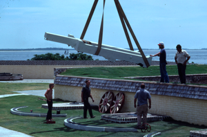Men installing cannon chassis, sea in background, Fort Moultrie, South Carolina