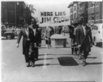"""[Pallbearers with casket walking in front of sign reading """"here lies Jim Crow"""" during the NAACP Detroit branch """"Parade for Victory""""]"""