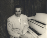 [Duke Ellington sitting next to white piano with hands clasped in lap. Black-and-white photoprint.]