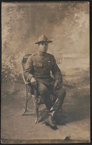 [Unidentified African American soldier in uniform with marksmanship qualification badge and campaign hat, with cigarette holder in front of painted backdrop]