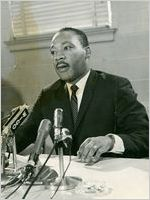 Martin Luther King, Jr., seated at desk, in front of microphones, Atlanta, Georgia, April 26, 1967(?)