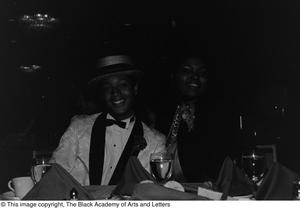 [Medium shot of an unidentified man and woman dressed in formal attire looking at the camera while siting at a dining table] Jack Evans Breakfast with JBAAL