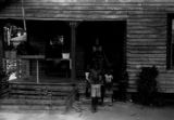 Children standing in front of a wooden house in Newtown, a neighborhood in Montgomery, Alabama.