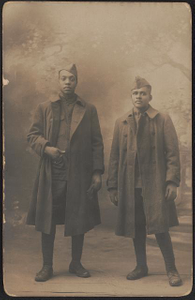 [Two unidentified African American soldiers in uniforms, greatcoats, and overseas caps in front of painted backdrop]