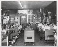 Mississippi State Sovereignty Commission photograph of the interior of Stanley's Cafe showing men eating while seated at tables, booths and counter, Winona, Mississippi, 1961 November 1