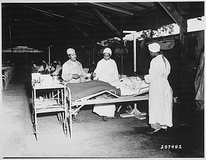 """""""Surgical ward treatment at the 268th Station Hospital, Base A, Milne Bay, New Guinea. Left to right: Sgt. Lawrence McKreever, patient; 2nd Lt. Prudence Burns, ward nurse; 2nd Lt. Elcena Townscent, chief surgical nurse; and an unidentified nurse."""""""