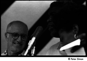 Jackie Robinson at the microphone standing next to an unidentified man