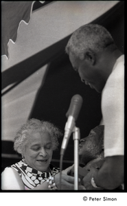 Jackie Robinson at the microphone, presenting a bust of Martin Luther King to unidentified woman
