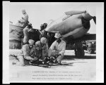 A serious task Members of the Armament Section busily engaged in mounting 30-caliber machine guns in the wings of a P-40 prior to its departure on a gunnery mission.