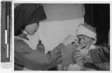 Sister Margaret, MM, washes an old woman's cancerous eye, Yeng You, Korea, ca. 1930-1950