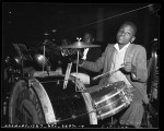 African American boy playing drum set at 1941 Children's Christmas party at May Co. department store in Los Angeles, Calif