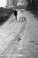 Man walking on a muddy street.