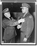 [Brig. Gen. Joseph E. Bastion pins the Distinguished Service Cross on Capt. Charles L. Thomas, commander of a tank destroyer company in France]