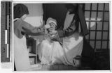 Maryknoll Sisters wash old woman's cancer-infected eye, Yeng You, Korea, ca. 1930-1950