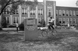 Police officer riding a bicycle at West End High School in Birmingham, Alabama, on the day the first African American students enrolled.