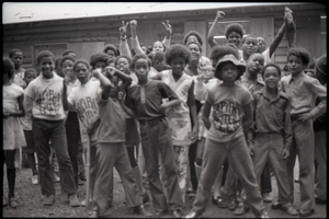 Inner City Round Table of Youth campers:group of African American campers, some wearing Spirit in Flesh t-shirts, standing outside summer camp cabins