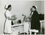 Captain Mary L. Petty, Chief Nurse, holding a glass bottle and showing it to 2nd Lieutenant Olive Bishop, who is writing on a small pad of paper
