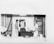 Mississippi State Sovereignty Commission photograph of three males standing inside the ticket office of the Trailways bus depot, Winona, Mississippi, 1961 November 1