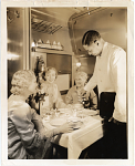 [African American waiter serving three women in Pullman car : photoprint]