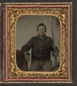 [Unidentified young soldier in Union uniform holding Colt revolving rifle in one hand and resting the other hand on a table]