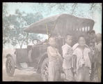 Four boys standing near a car, China, ca. 1918-1938