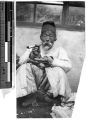 Elderly Korean man sitting under a window smoking a pipe, Korea, ca. 1920-1940