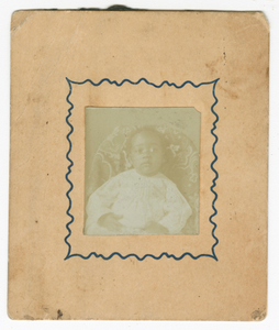 Photograph of a baby dressed in white and sitting in a chair