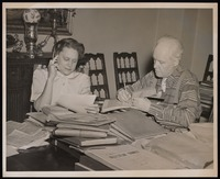 Photograph of Grace Nail Johnson and Carl Van Vechten going over James Weldon Johnson's papers
