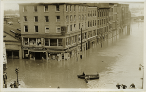 Aftermath of the great Hartford Flood: Flood waters on State Street (Manchester Leaf Tobacco Co. Building to City Paper Co.) with row boat on the streets and men on roof