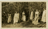 Individuals Posed Near Trees with Costumes and Head Wreaths